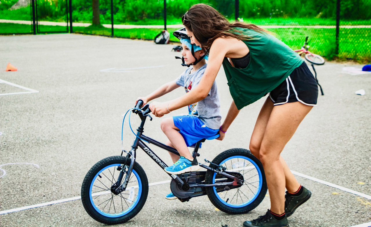 camp instructor teaching boy how to ride a bike